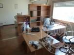 Immagine di scrivania ad angolo in laminato chiaro. N. 6 librerie in laminato, scaffalatura legno composta da 10 montanti e 58 ripiani, mobile rack contenente n.2 server marca Intel, N. 3 gruppi di continuita' marca Evo. N. 2 scrivanie legno bianco, N. 1 dattilo, n.1