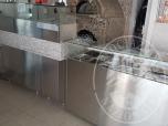 Immagine di Bancone composto da due elementi con struttura e ante in acciaio, ripiano in granito e vetro, contenitori in acciaio